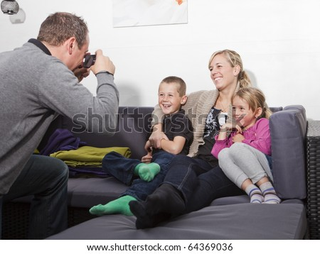 Father taking a photo of his family siting in the sofa - stock photo