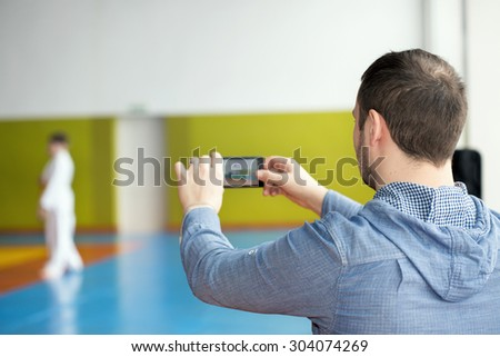 Father taking photo of his kid training martial arts - stock photo