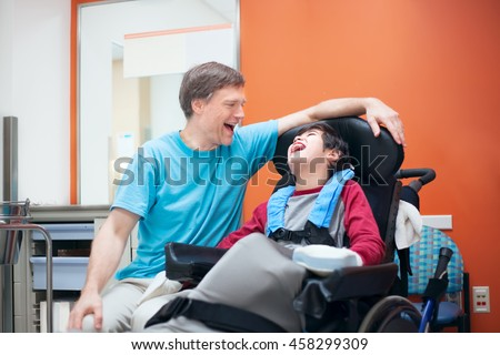 Father talking with disabled biracial son sitting in wheelchair while waiting in doctor's office, laughing together. - stock photo