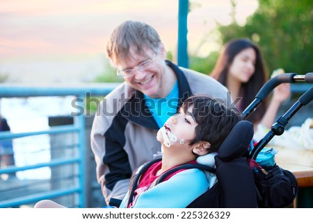 Father talking with disabled son in wheelchair outdoors by lake - stock photo