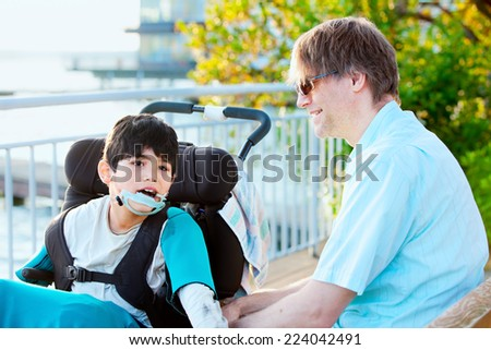 Father talking with his disabled son in wheelchair outdoors - stock photo