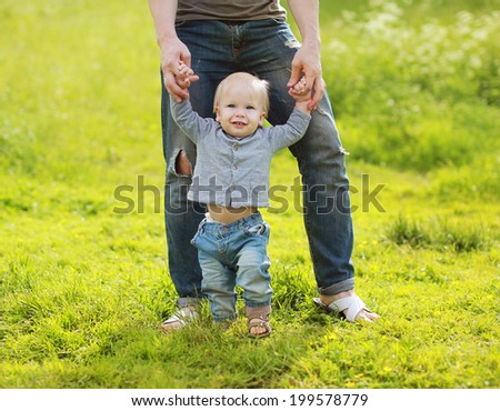 Father teaches baby to walk - stock photo