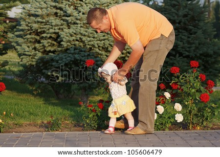 Father teaches her beautiful little daughter to walk on the background of rose bushes - stock photo