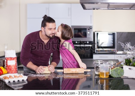 Father teaches his daughter to cook at home in the kitchen. Stock image. - stock photo