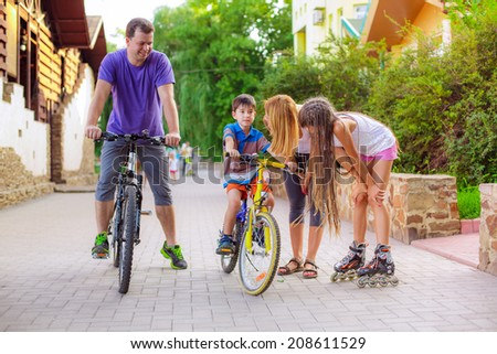 father teaches his son to ride a bike - stock photo