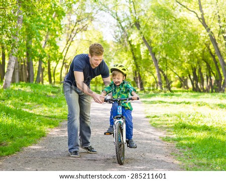 father teaches his son to ride a bike in park - stock photo
