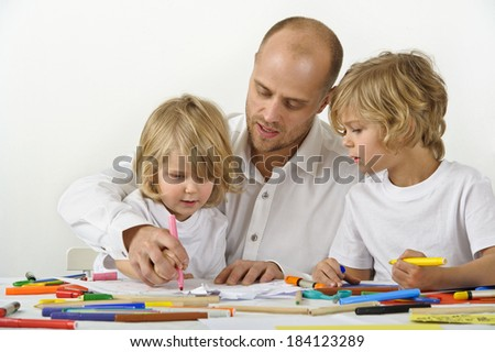 Father teaches his young son how to hold a pen - stock photo