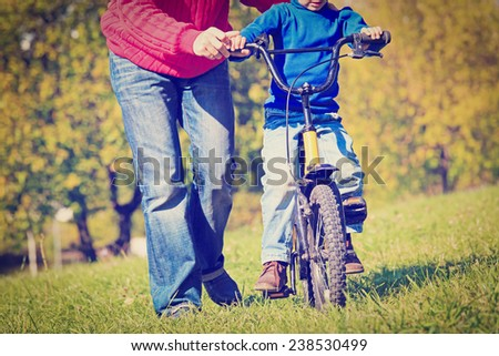father teaches son to ride bicycle outdoors - stock photo