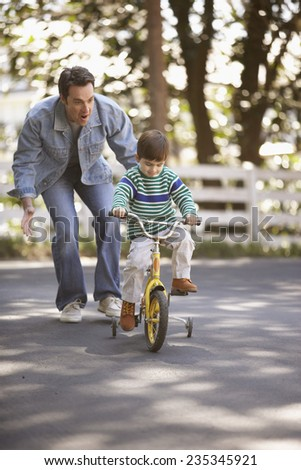 Father Teaching Boy Riding a Bicycle - stock photo
