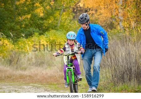Father teaching child to ride bike in autumn park, family sport  - stock photo