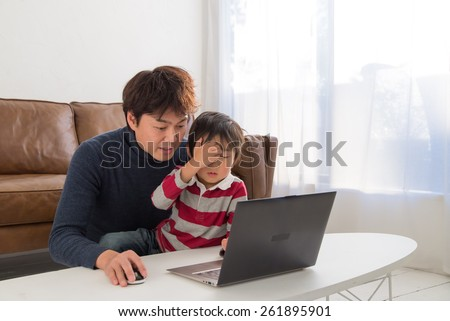 Father teaching child with a laptop - stock photo