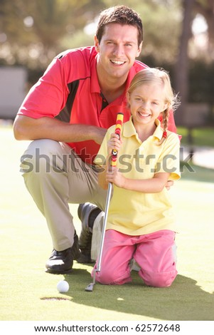 Father Teaching Daughter To Play Golf On Putting On Green - stock photo