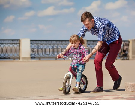 Father Teaching Daughter To Ride Bike - stock photo