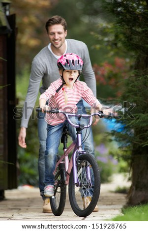 Father Teaching Daughter To Ride Bike In Garden - stock photo