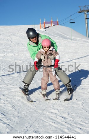 Father Teaching Daughter To Ski Whilst On Holiday In Mountains - stock photo