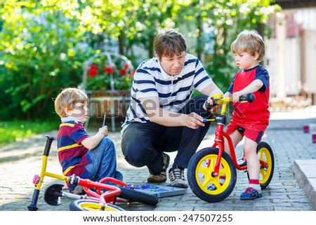 Father teaching his little sons to repair bikes, showing to change a wheel. Family working together outdoors, on warm sunny day. Active leisure with kids. - stock photo