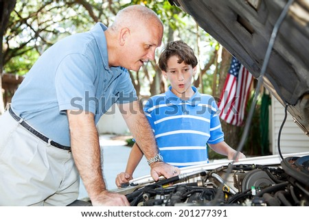 Father teaching his son how to do auto repair.   - stock photo