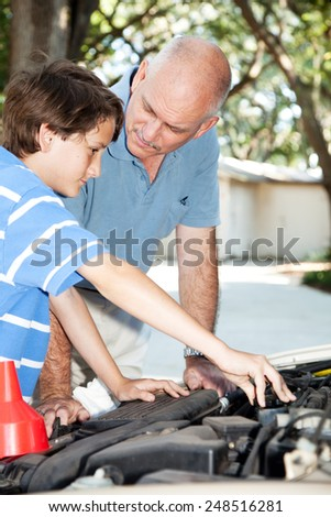Father teaching his son how to do auto repairs, oil change, etc.   - stock photo