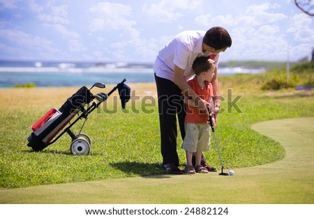 Father teaching his son how to play golf. - stock photo