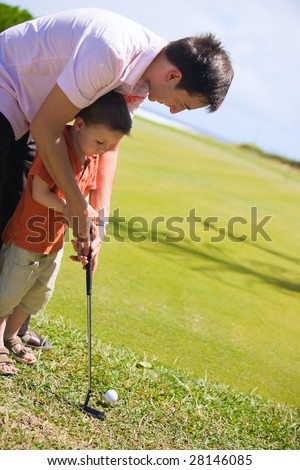Father teaching his son how to play golf - stock photo