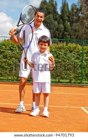 Father teaching his son how to playing tennis - stock photo