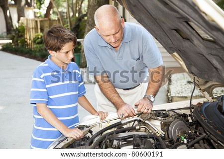 Father teaching his son how to repair the car. - stock photo