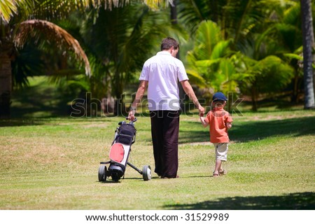 Father teaching his son to play golf. - stock photo