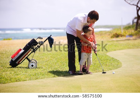 Father teaching his son to play golf - stock photo