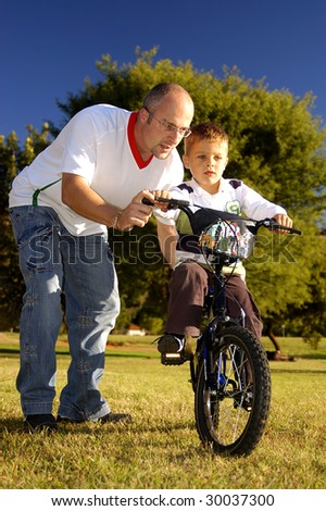 Father teaching his son to ride bicycle - stock photo