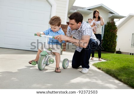 Father teaching his son to ride tricycle while wife standing in background - stock photo