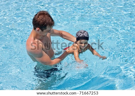 Father teaching his son to swim - stock photo