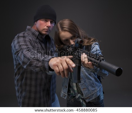 Father teaching his teenage daughter how to shoot a rifle to defend herself. Doomsday Preparedness. - stock photo