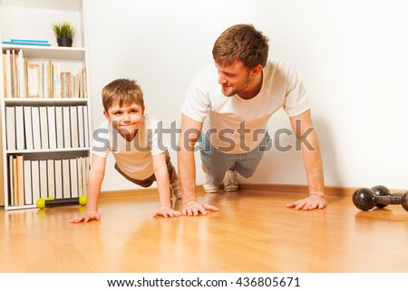 Father teaching kid son doing push-ups exercises - stock photo