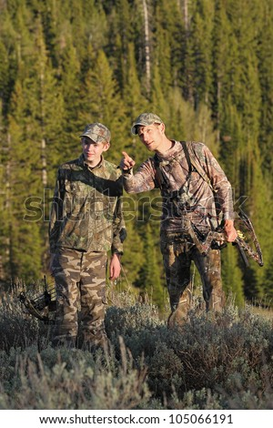 father teaching son during archery deer hunt - stock photo
