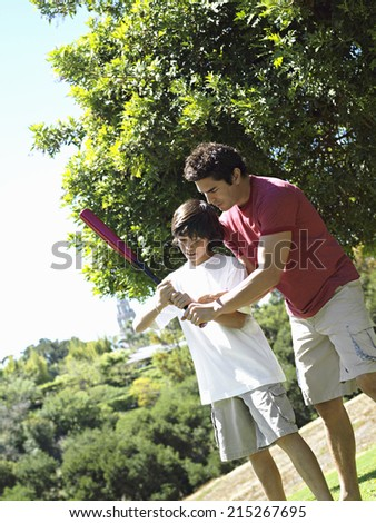 Father teaching son (10-12) how to hold baseball bat, standing on grass in park (tilt) - stock photo