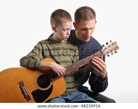 father teaching son how to play acoustic guitar - stock photo