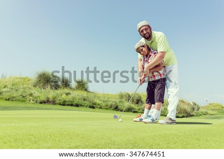 Father teaching son playing golf at club - stock photo