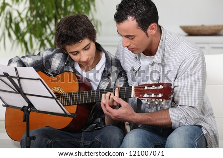 Father teaching son the guitar - stock photo
