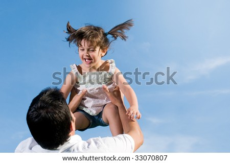 Father throw in air his little daughter in a clear blue sky with copy space for your text - stock photo