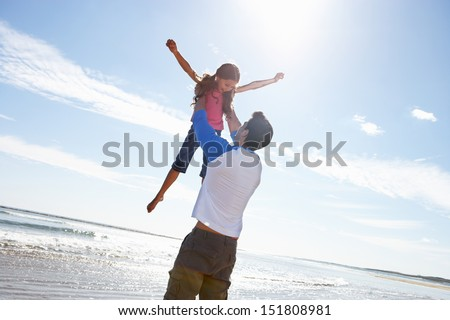 Father Throwing Daughter Into Air On Beach - stock photo