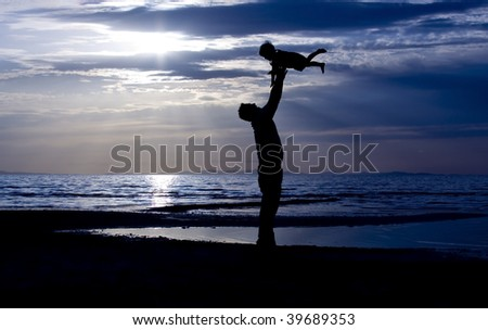Father throwing his kid up in the air on the beach - stock photo