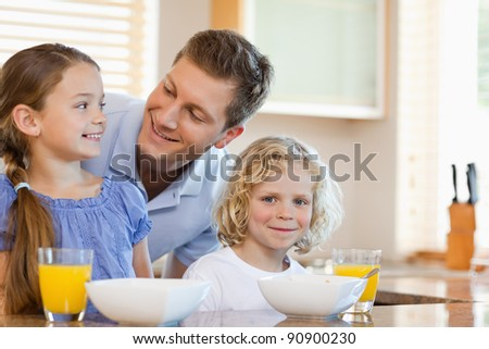 Father together with his children behind the kitchen counter