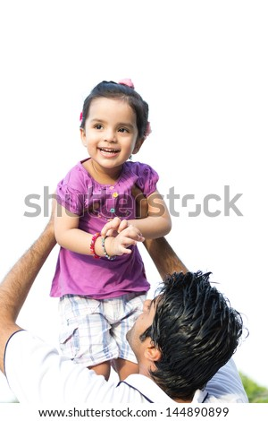 father tossing up the daughter in air, happy indian man tossing his daughter in the air - stock photo