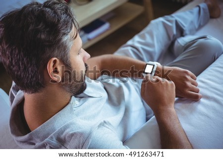 Father using a smart watch at home
