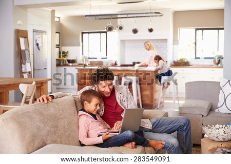 Father using computer with son, family in background - stock photo