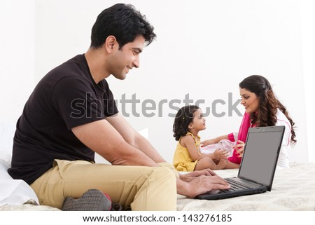 father using the laptop with mother and daughter playing in the background - stock photo