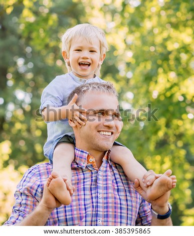 Father walking in the park with son sitting on his shoulders.