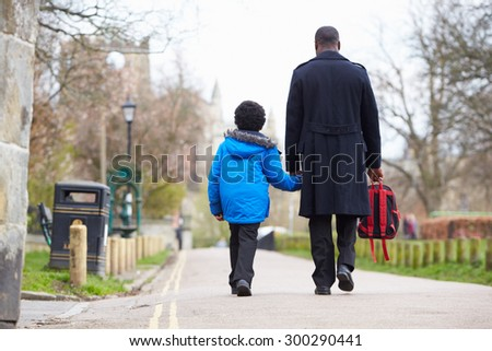 Father Walking Son To School Along Path - stock photo