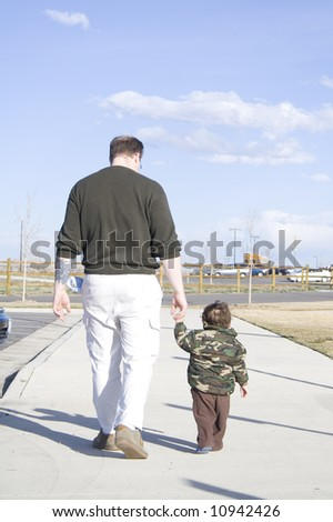 Father walking with baby son at the park with blue sky - stock photo