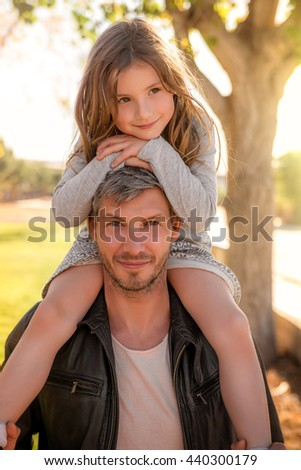 father walking with daughter sunset - stock photo